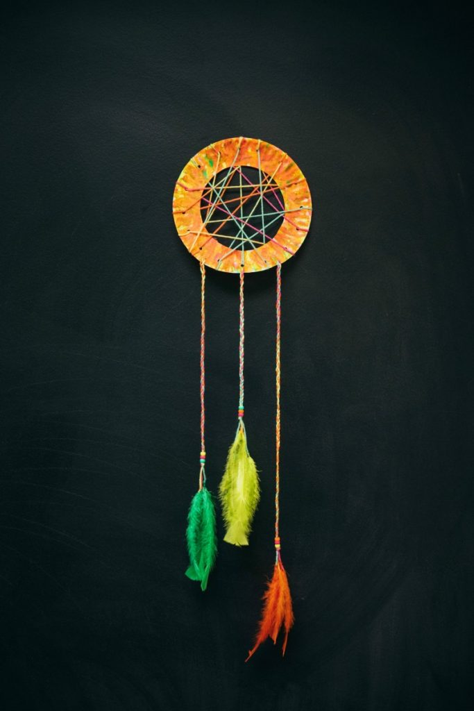 Pretty paper plate beaded dream catchers designed with yarn, beads, and feathers.
