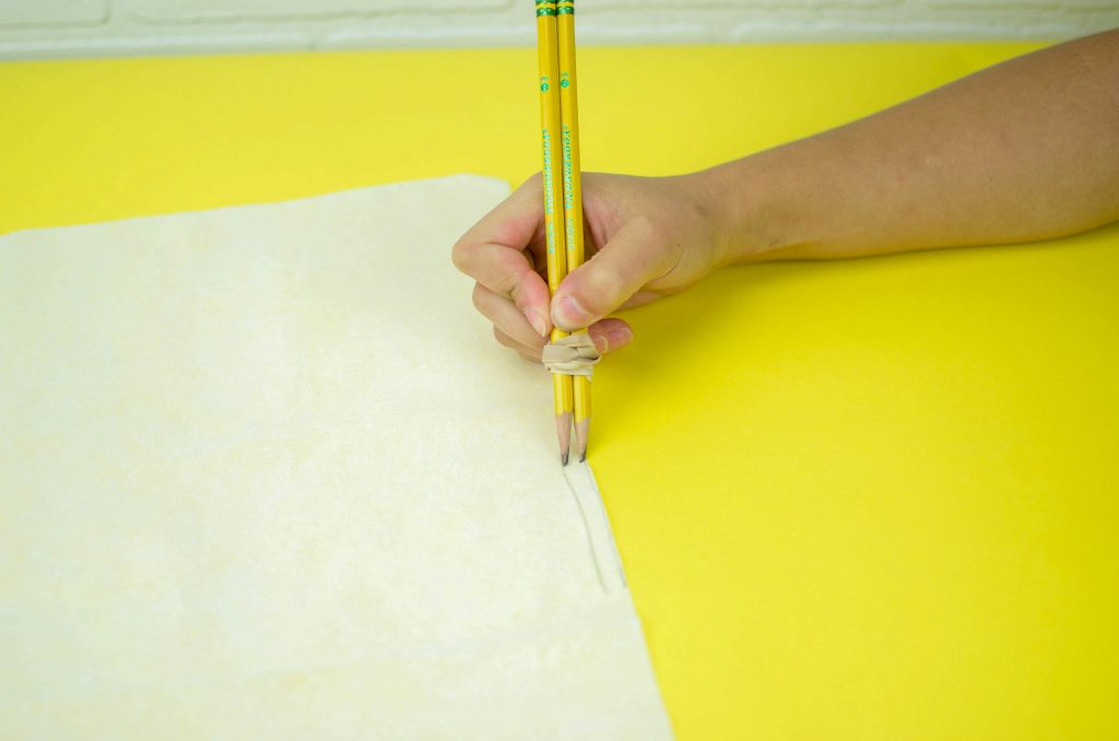 attach two pencils together with a rubber band to mark sewing lines