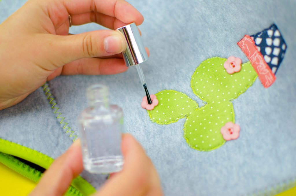 use clear nail polish to secure button threads