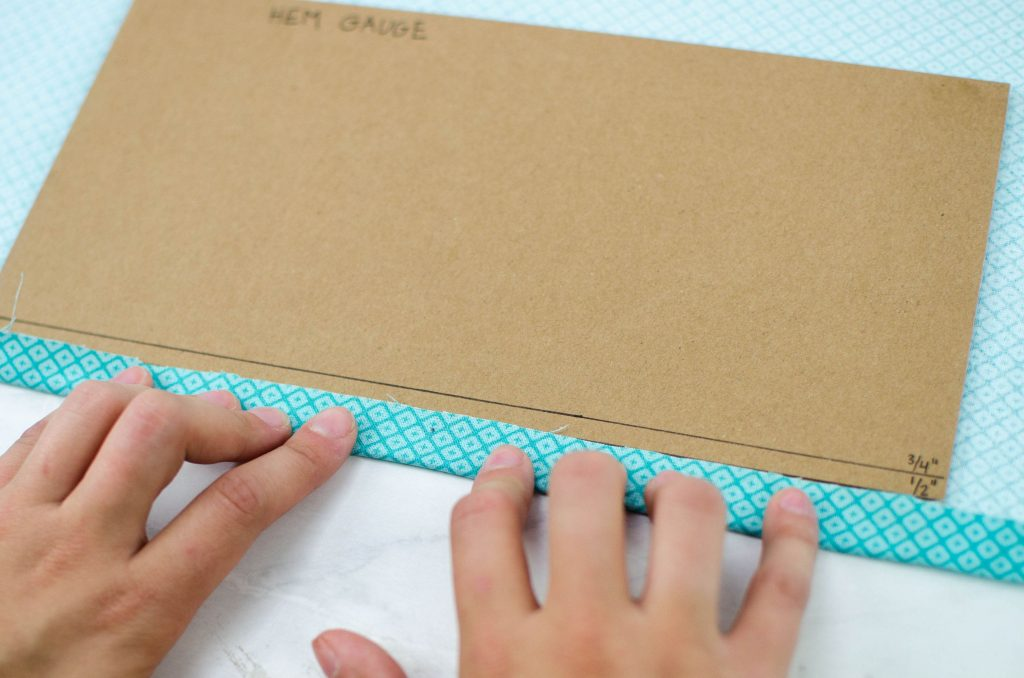 fold fabric over your hem gauge to the 1/2 inch mark