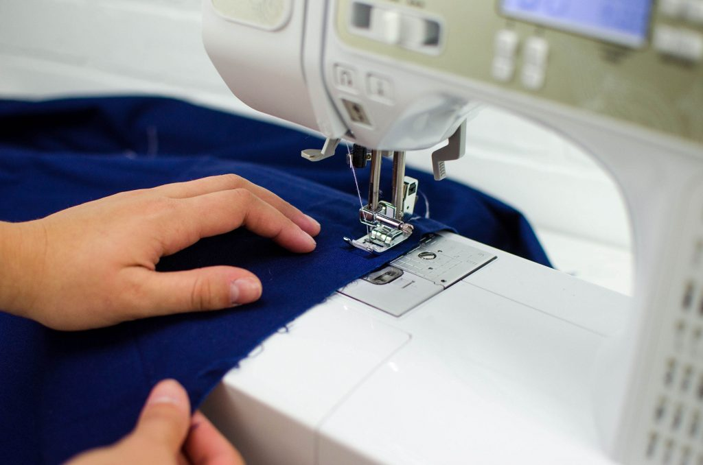 using a sewing machine to stitch a line 1/4 inch away from desired seam allowance for rolled hem
