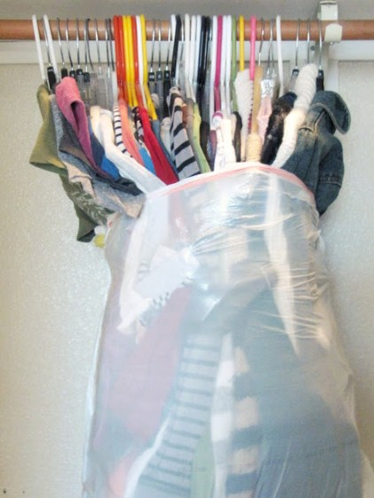 clothing on hangers stuffed into a garbage bag
