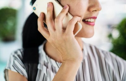 call the utility companies as soon as you know your moving date - image of a woman talking on a phone