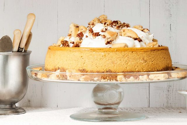 Pumpkin cheesecake with pecan cookie crust topped with whipped cream and garnish with cookies and pecans