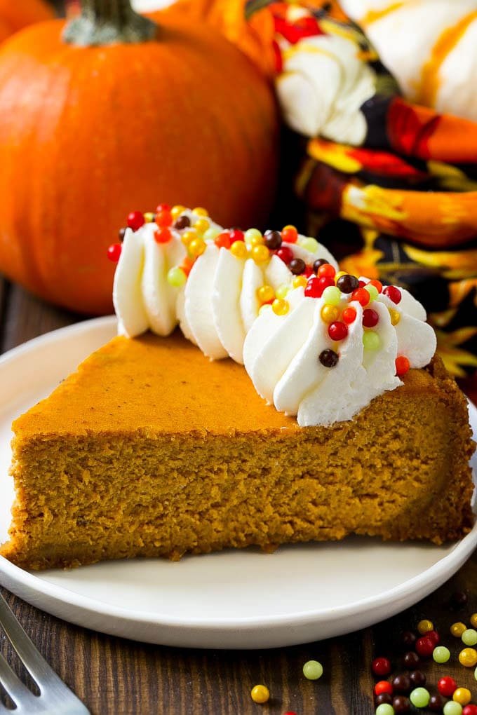 A slice of pumpkin cheesecake with whipped cream and sprinkles
