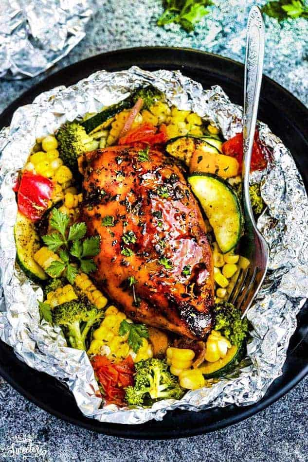 Perfectly tender chicken grilled with fresh summer veggies and coated in a delicious sweet and tangy barbecue sauce foil packets