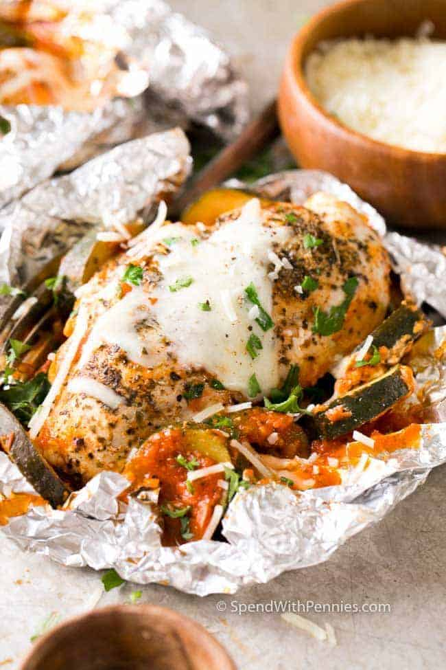 Chicken parmesan foil packets sprinkled with freshly grated parmesan and garnished with fresh parsley.