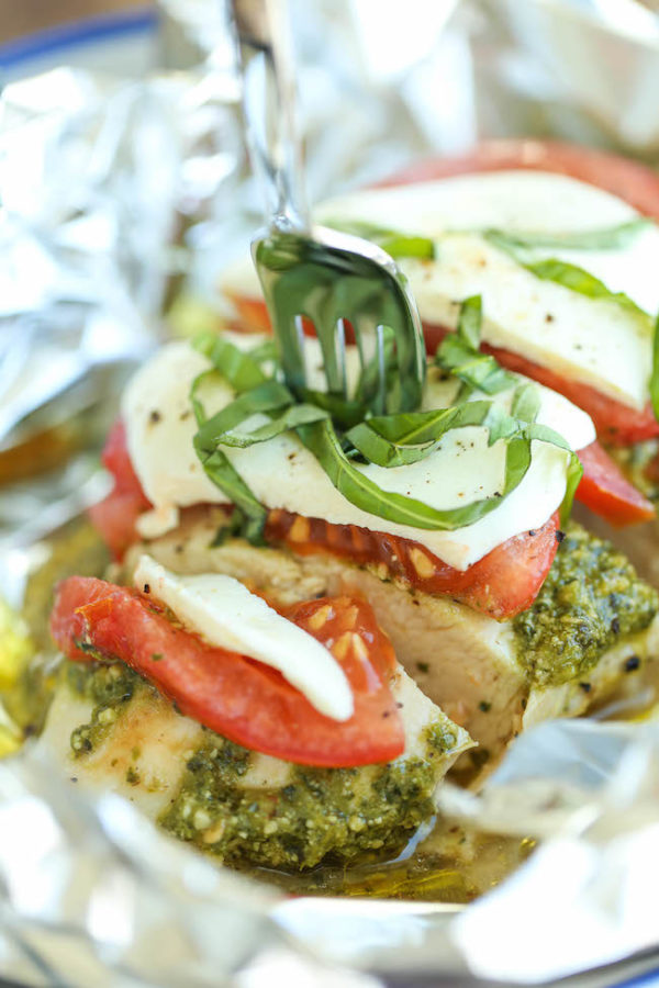 Pesto caprese chicken in foil garnished with basil