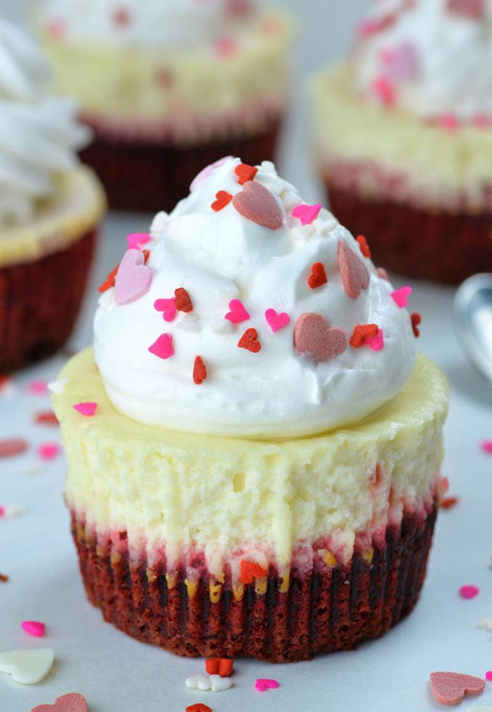 Red velvet cheesecake cupcakes topped with whipped cream and garnished with festive heart shape sprinkles