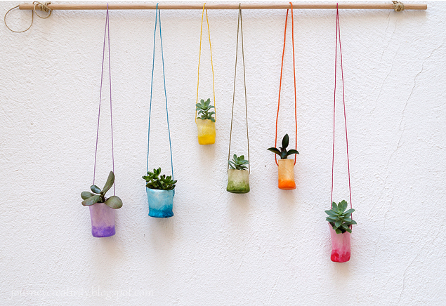 air dry clay plant pots painted in rainbow colors and hanging from a dowel