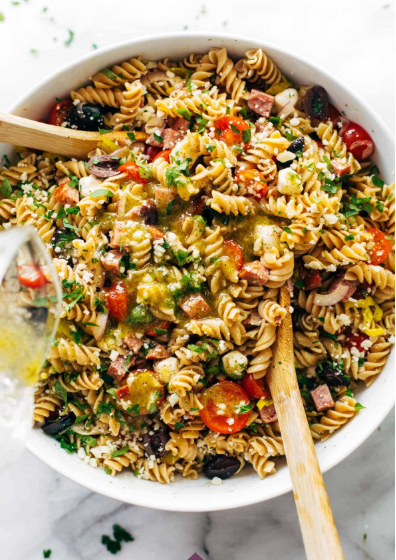 A bowl of Italian pasta salad with rotini, juicy tomatoes, fresh mozzarella, red onion, salami, olives, herbs, and a drench of quick homemade Italian dressing.