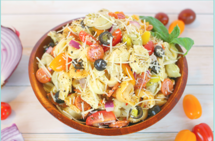 Easy tortellini pasta salad loaded with salami, tomatoes, olives, banana peppers topped with Italian dressing and shredded Parmesan cheese