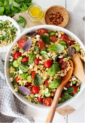 Pasta salad with cherry tomatoes, feta cheese, arugula, chickpeas, pine nuts & cucumber, and lots of fresh parsley and basil
