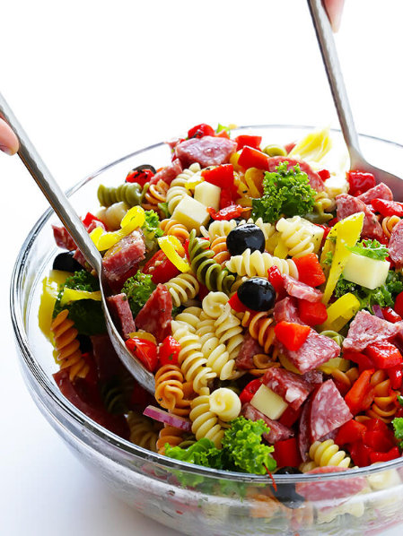 Antipasto salad made with salami, diced cheese, cherry tomatoes, olives, artichoke hearts, pepperoncini, roasted red peppers, kale and red onion.