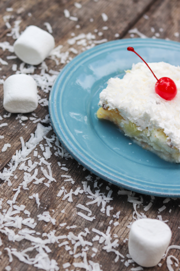 Tropical summer cake topped with whipped topping and coconut.
