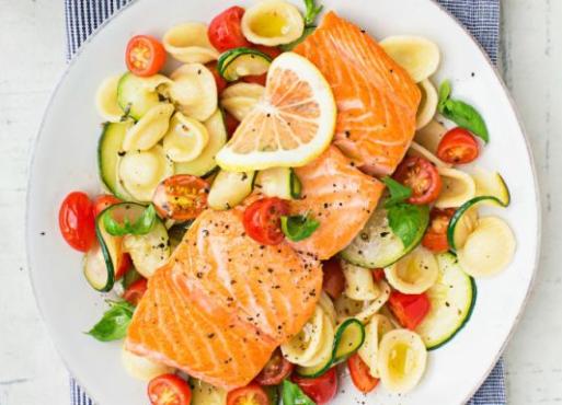 Warm pasta salad with salmon and sliced lemon on top