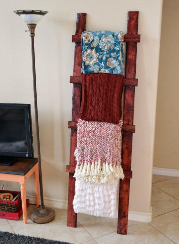 wooden ladder holding throw blankets