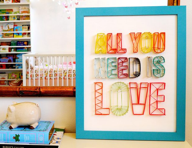 Handmade string art sign that says All you need is love