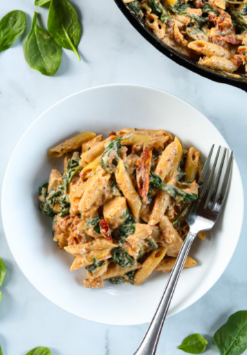 A plate of creamy tuscan chicken pasta