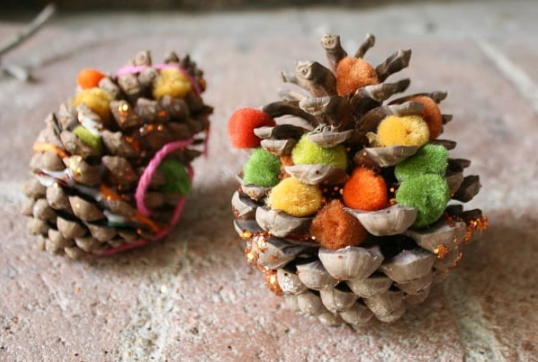 Pine cones decorated with pompoms and glitters
