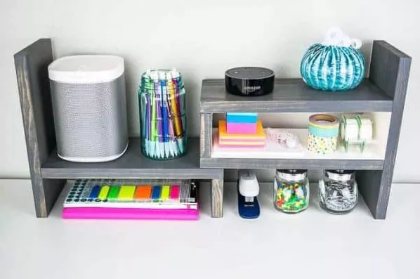 A color gray adjustable desktop organizer with some stuff on it