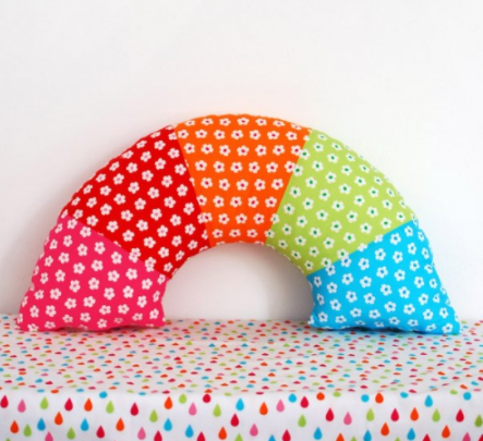 A rainbow pillow with white flowers design on it