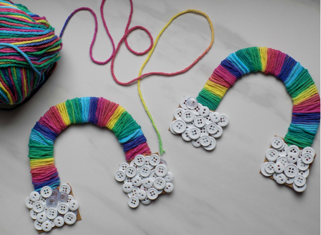A gradient yarn rainbow with a handful of multi-size white buttons on each end