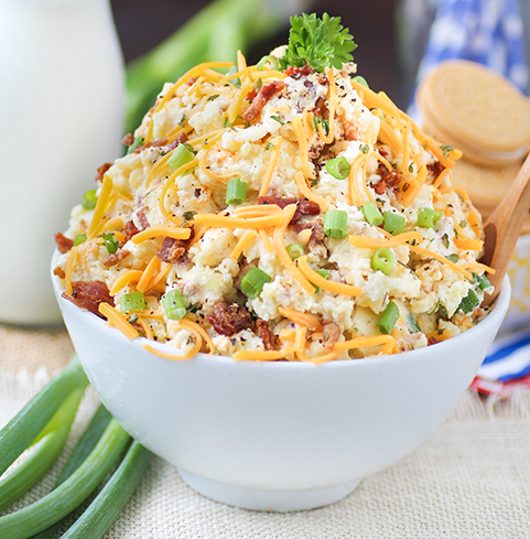 Loaded baked potato salad served cold with pieces of bacon, green onions, and cheddar cheese