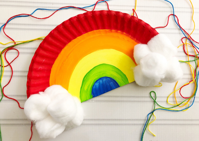 A rainbow craft made from a paper plate with some rainbow strings and cloud on it