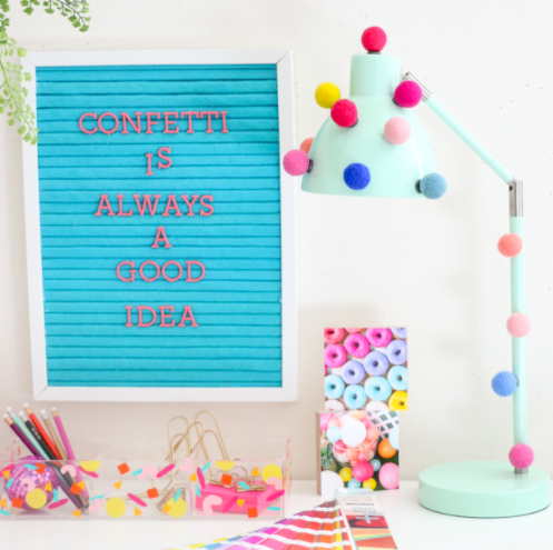 Cute mint lamp decorated with colorful pompoms and a magnet board with text saying Confetti is always a good idea