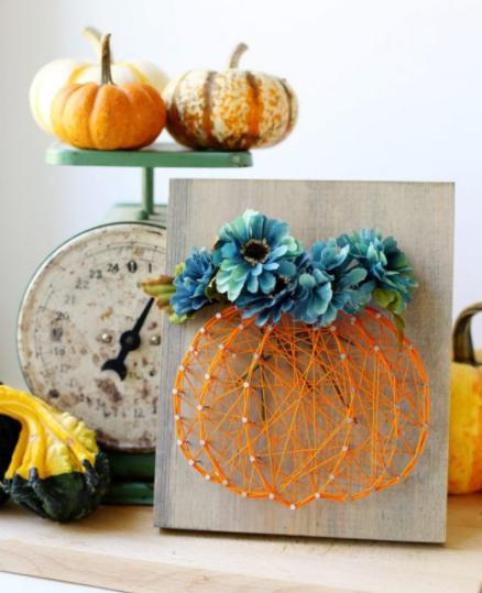 beautiful flowers added to a string art pumpkin
