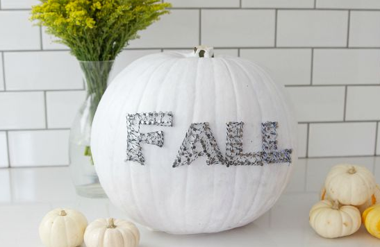 A pumpkin painted white decorated a string art that says Fall