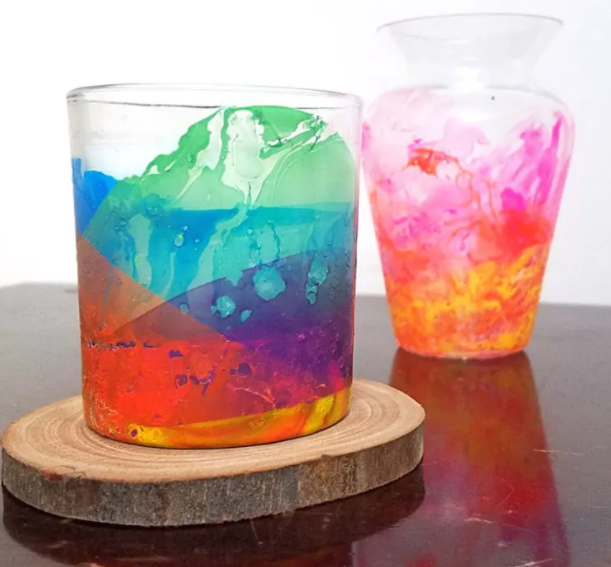 A candle holder made from glass vase painted in rainbow color