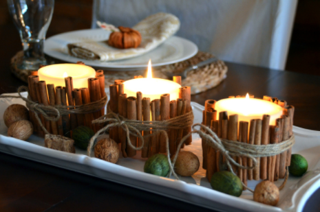 Lighted candles wrapped with cinnamon sticks fall centerpiece