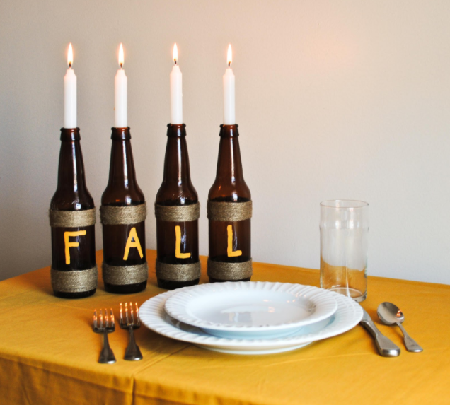 4 brown glass bottles wrapped with twine and has a F A L L letter in each bottle and lighted candles plunked on them