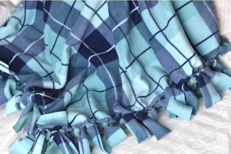 Stripe color blue fleece blanket with a tied fringe edge