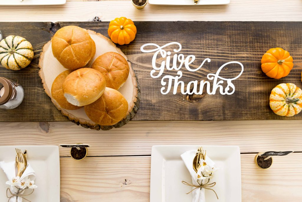 Wooden table runner with text on it saying give thanks, and some breads and pumpkins on top of it