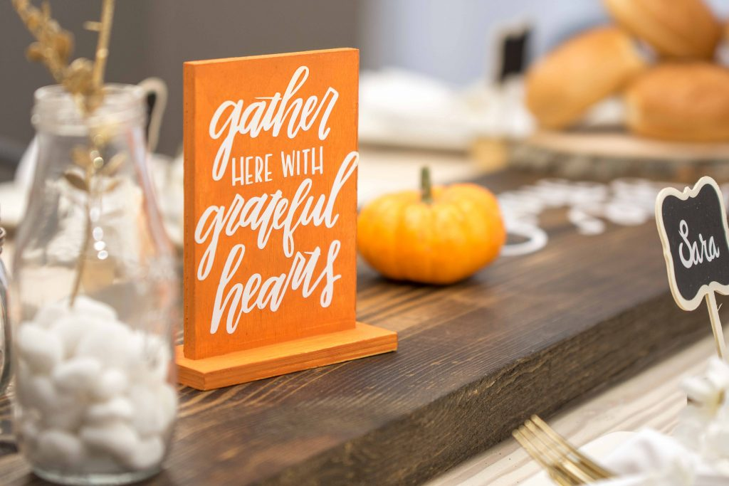 Sign centerpiece with text saying gather here with grateful hearts