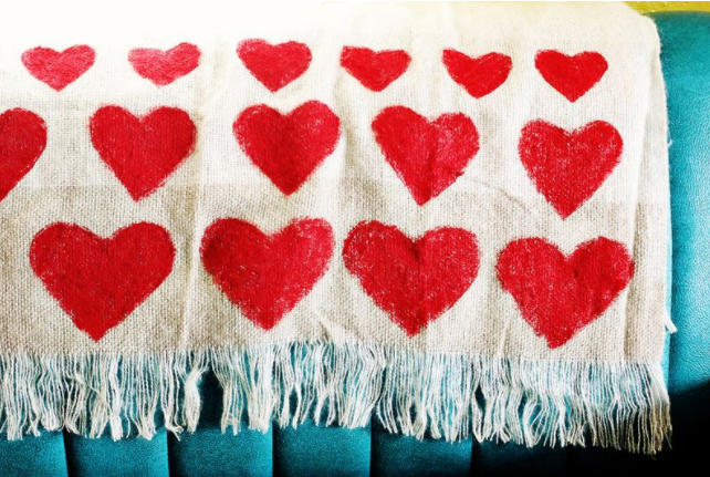 Throw blanket with a heart shapes painted to it