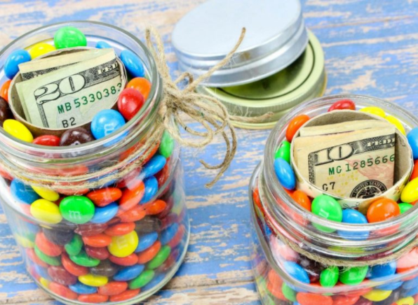Two jars full of M & M's that has a hidden paper towel tubes on the middle with a $20 and $10