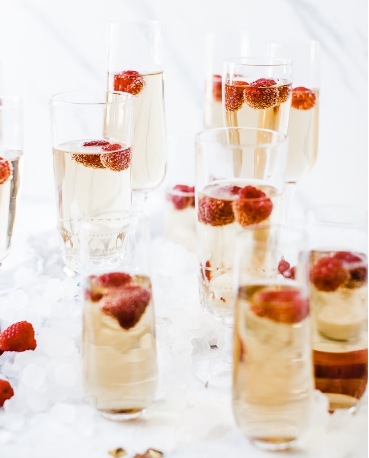 A fancy bubbly glass of mock champagne with raspberries