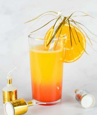 New Year sunrise mocktail on a glass with a sliced of orange and a straw and foil cocktail sticks.