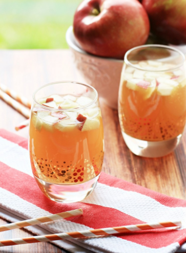 Apple pie punch on a glass with fresh sliced apples on top