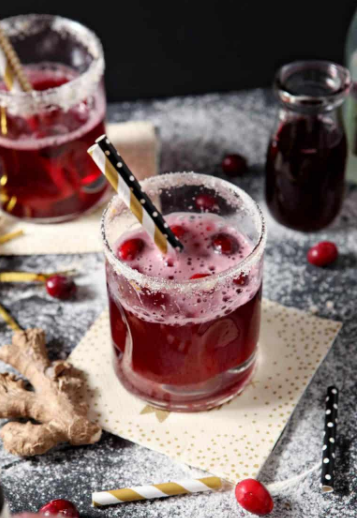 Sparkling Ginger Cranberry Mocktail on a glass with some fresh cranberries
