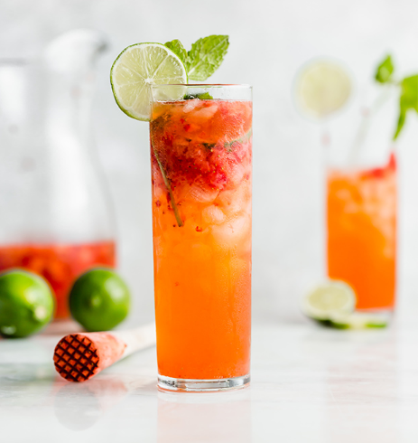 Strawberry lime mojito mocktail on a glass with sliced lime and mint leaves on top