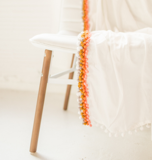 Summer DIY throw blanket with a color pink, orange and mustard trim pompoms on the edge