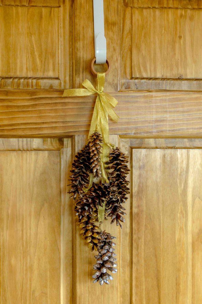 A pine cone wreath door hanging