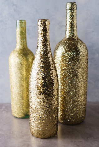 Wine bottles that have been painted gold and have glitter added to use as centerpieces