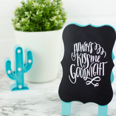 A vinyl chalkboard sign with text saying Always Kiss Me Goodnight