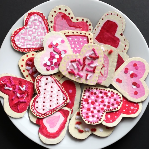 Valentines cookie made from cardboard painted red and pink with yarn sprinkles, pipe cleaners and paper confetti.